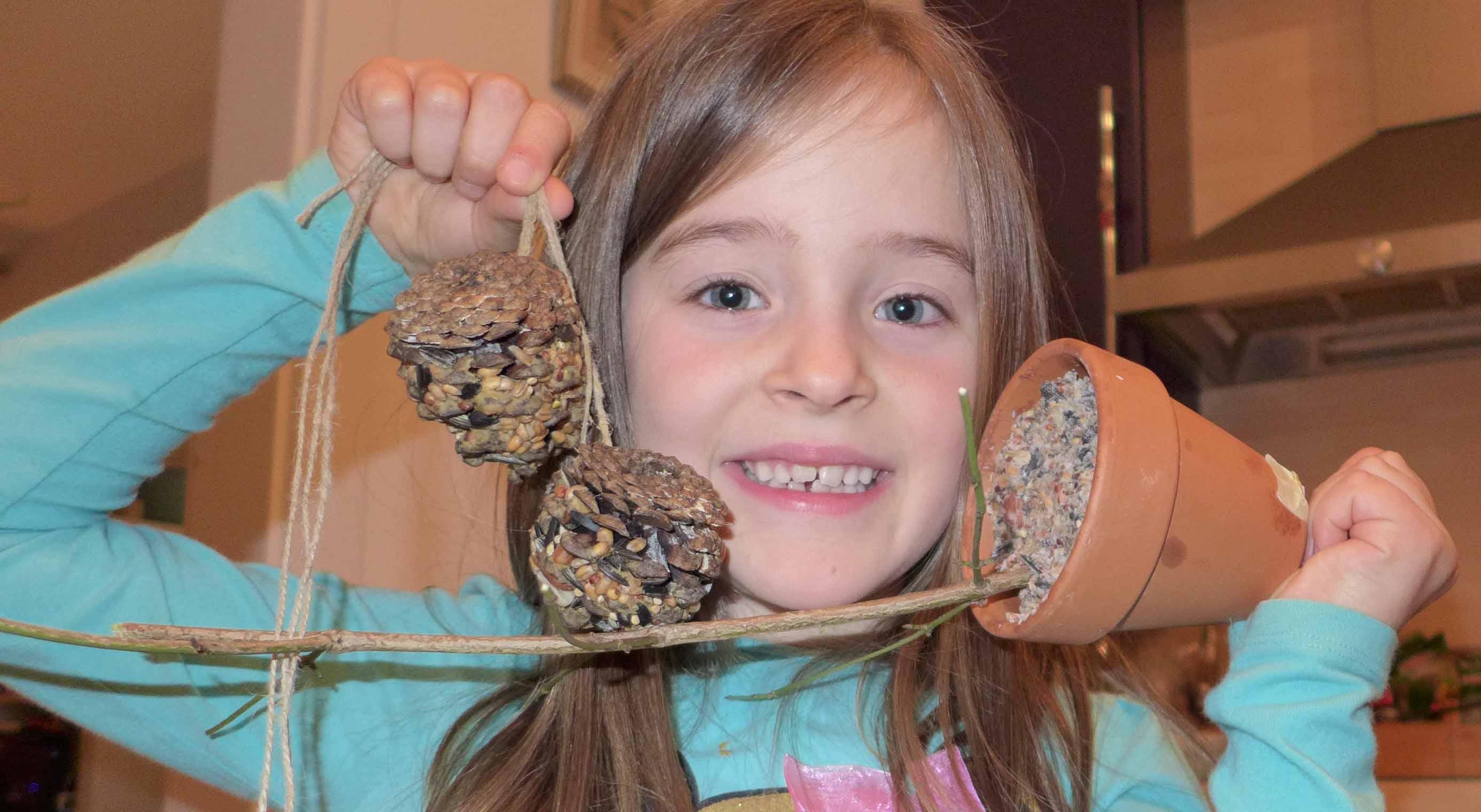 Lilia zeigt stolz ihre selbst gebastelte Futterglocke und Futterzapfen!