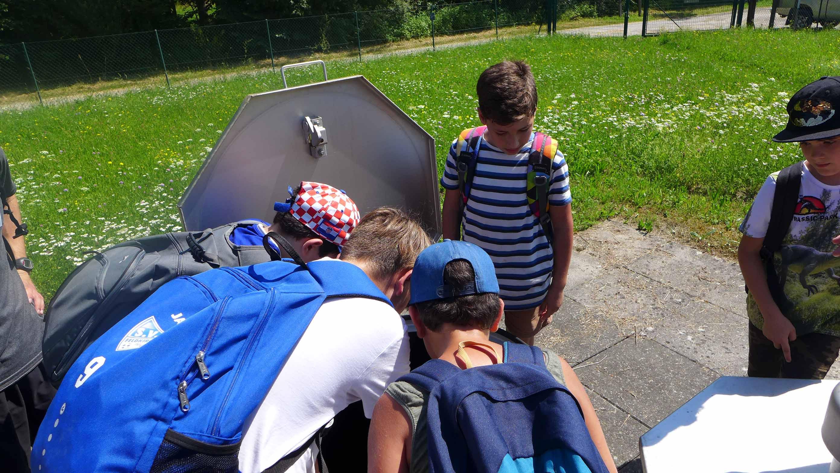Schülerinnen und Schüler werfen einen Blick in den 5m tiefen Brunnen ...